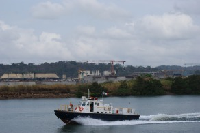 A speedboat passes a still ship